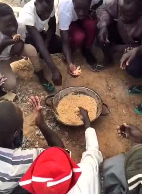一群非洲人围在一起用手抓面条吃图片