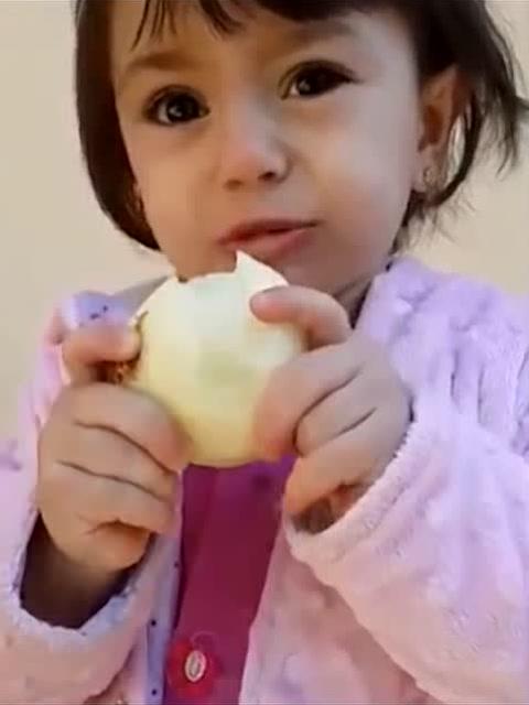 小女孩强忍着眼泪吃洋葱,辣的想哭却又啃了一口,被她萌哭了