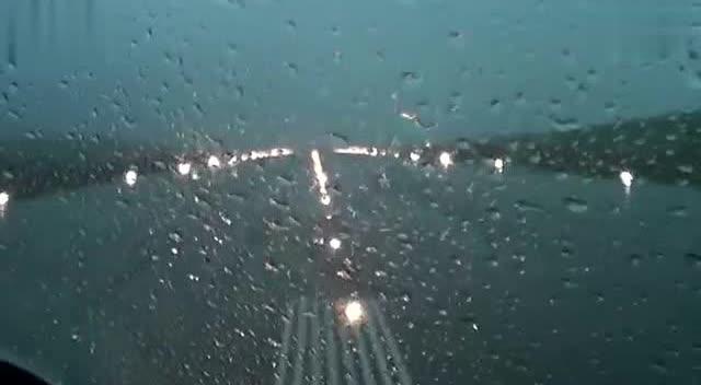 驾驶员在下雨天驾驶飞机降落的情景